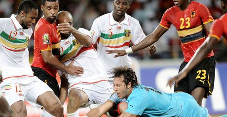 Tight contest: Angola keeper Carlos Fernandes dives for the ball.