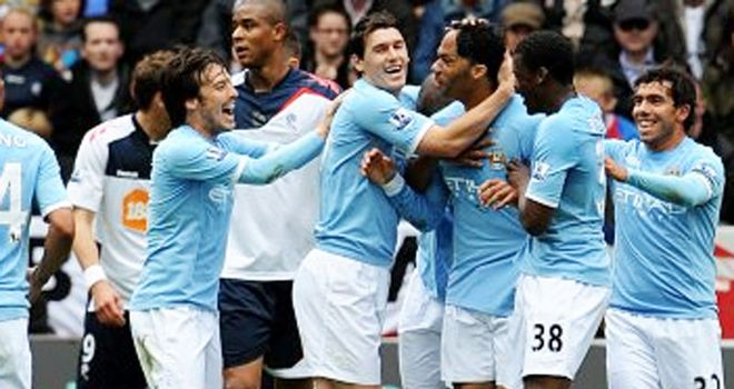 Lescott: Mobbed by team-mates after heading opening City goal