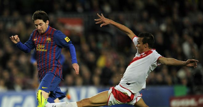 Pedro Botelho (R) makes a sliding tackle on Barcelona's Lionel Messi (L)