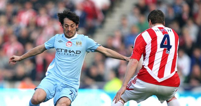 Manchester City's David Silva and Stoke's Robert Huth fight for the same ball