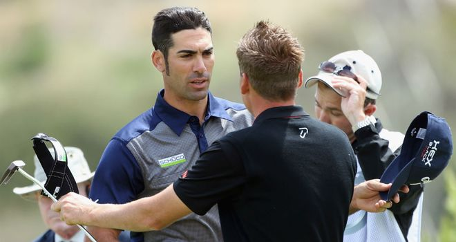 Alvaro Quiros (L) is congratulated by Ian Poulter (R) after his victory over the Englishman