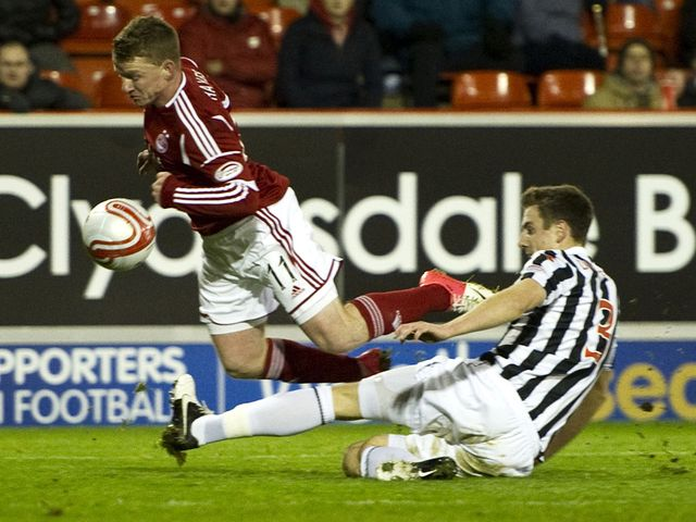 Jonny Hayes is challenged by Paul Dummett