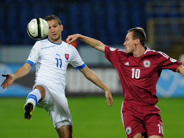 Bakos tries to keep the ball away from Visnakovs.