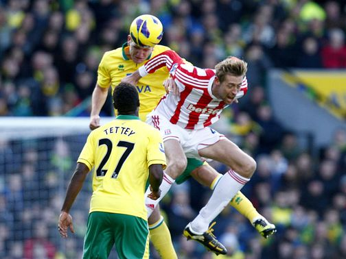 Michael Turner and Peter Crouch go for a high ball