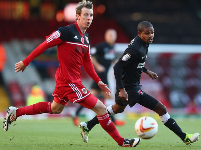 Martyn Woolford and Bradley Pritchard vie for the ball