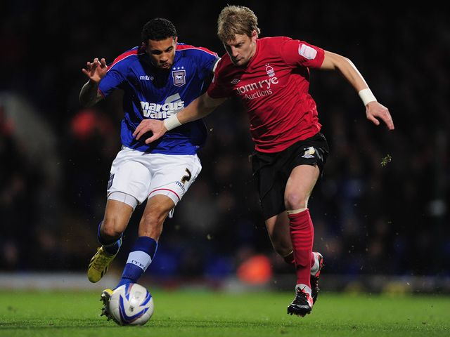 Carlos Edwards and Dan Harding battle for the ball