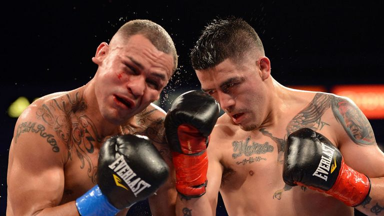 Mike Alvarado (L) takes a right hand from Brandon Rios