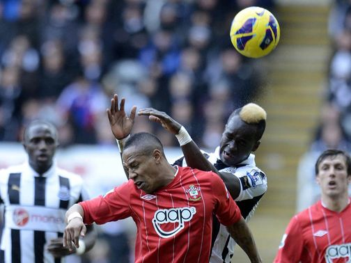 Cheick Tiote jumps for the ball with Nathaniel Clyne