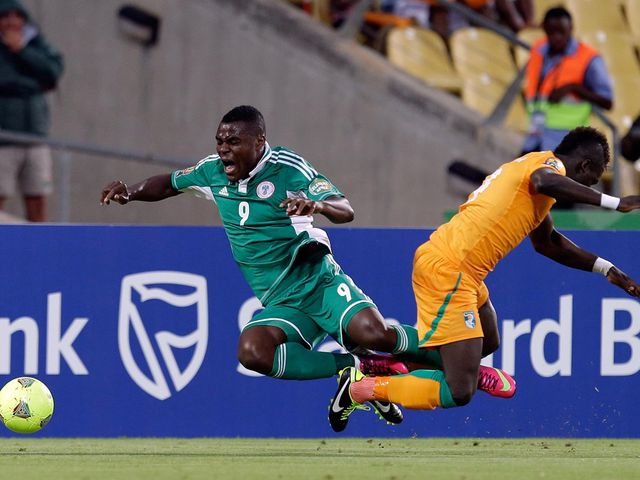 Emenike and Tiote take a tumble.