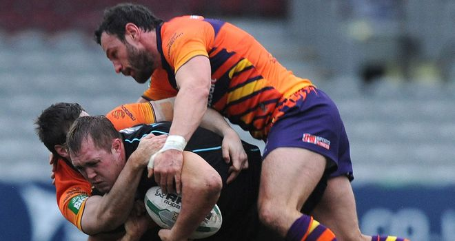 The Widnes defence wraps up Broncos' Scott Wheeldon