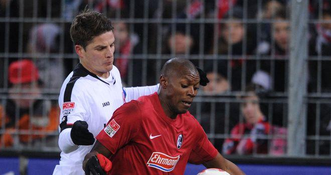 Freiburg's Karim Guede holds off Pirmin Schwegler