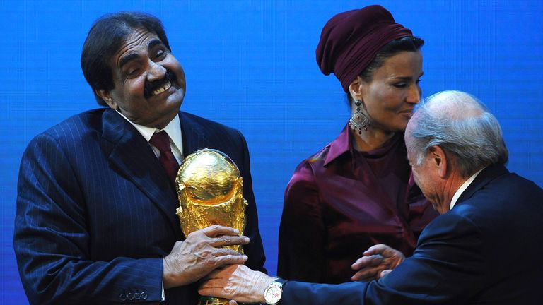FIFA president Sepp Blatter hands the World Cup to Sheikh Hamad bin Khalifa Al-Thani