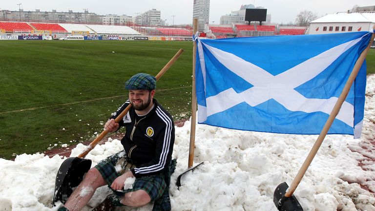 Scotland supporters helped clear the snow-covered pitch in Novi Sad