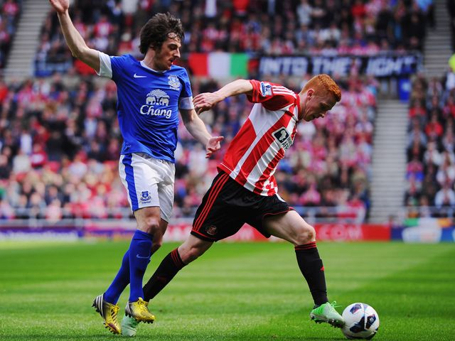 Jack Colback of Sunderland holds off Leighton Baines