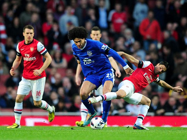Marouane Fellaini and Mikel Arteta battle for the ball.