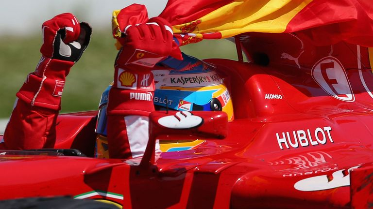 A jubilant Alonso celebrates victory of his home race with a Spanish flag. The naughty so-and-so.