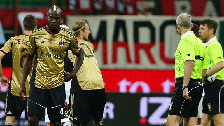 Balotelli and his AC Milan team-mates wait for Sunday's match to be restarted