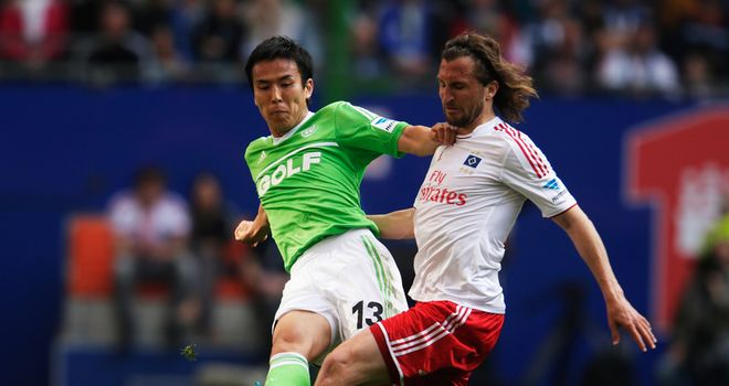 Petr Jiracek of Hamburg and Makoto Hasebe of Wolfsburg battle for the ball