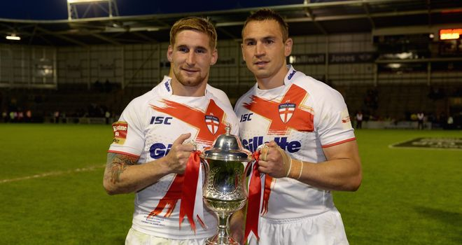 Sam Tomkins (l) and England captain Kevin Sinfield lift the trophy after victory at The Halliwell Jones Stadium