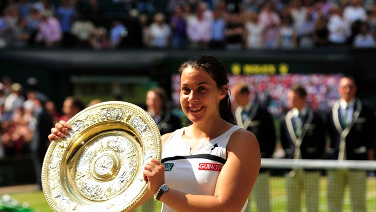 France's Marion Bartoli poses with the winner's Venus Rosewater Dish after beating Germany's Sabine Lisicki in their women's singles final