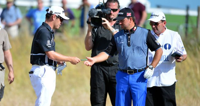 Louis Oosthuizen hands Graeme McDowell his card after being forced to quit