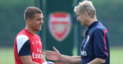 Arsene Wenger: Talks to Lukas Podolski during Friday's training session