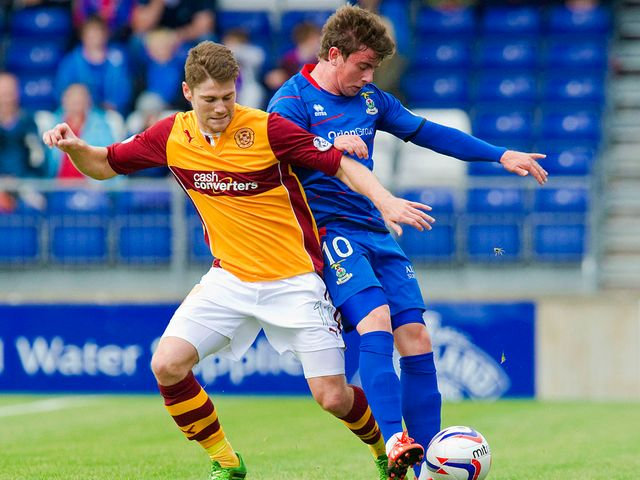 Iain Vigurs battles for the ball with Aaron Doran