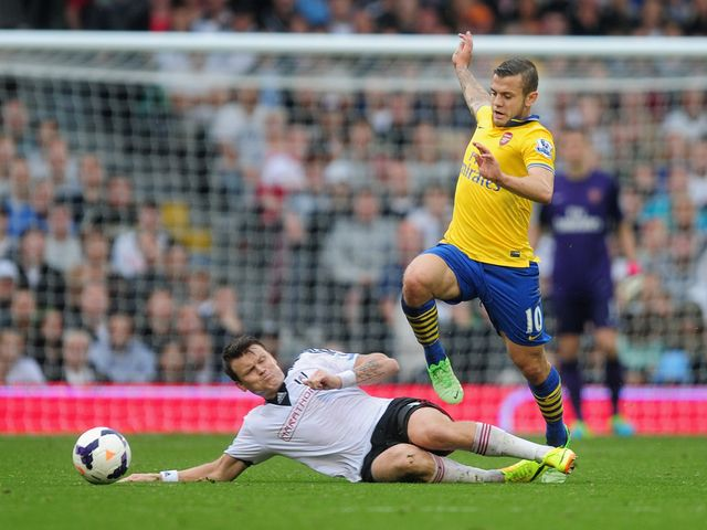 Wilshere jumps over Riise's challenge.