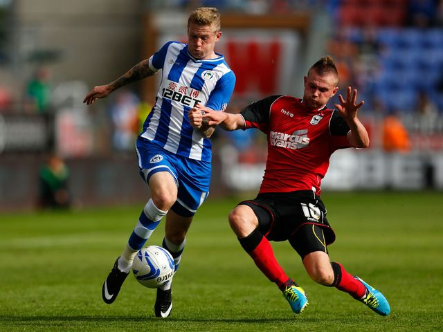 Wigan's James McLean (l) tussles with Ryan Tunnicliffe
