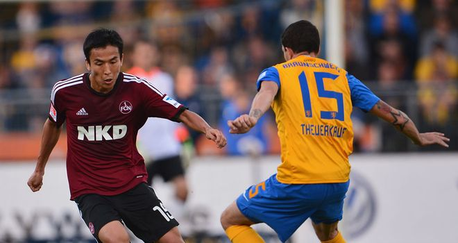 Makoto Hasebe is challenged by Norman Theuerkauf