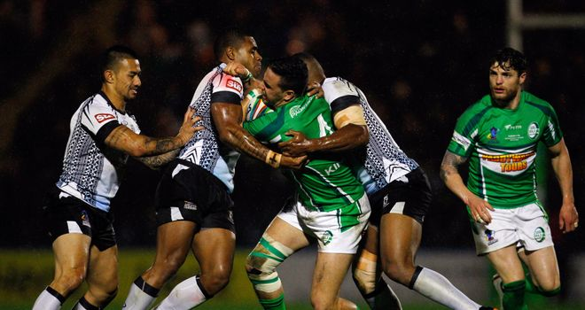 Apirana Pewhairangi of Ireland is tackled by Fiji's Kevin Naiqama and Waisale Ligani Naiqama