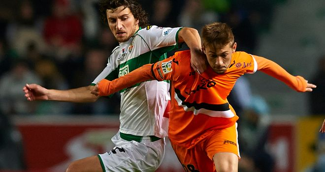 Stevanovic of Elche competes for the ball with Fede of Valencia