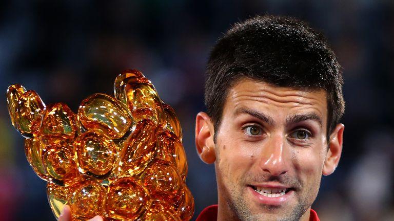 Novak Djokovic poses with the trophy in Abu Dhabi
