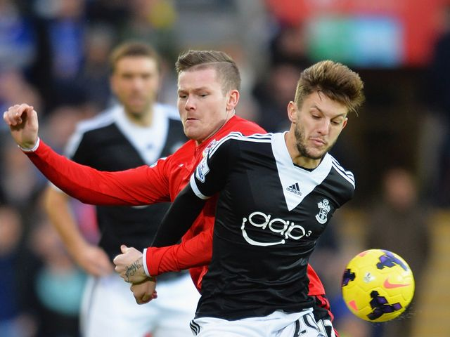 Adam Lallana holds off Aron Gunnarsson