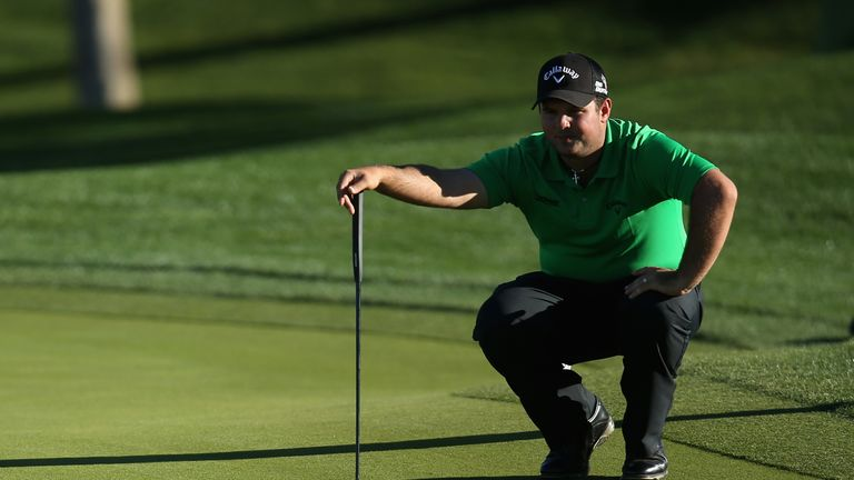 Patrick Reed lines up a putt on the ninth hole