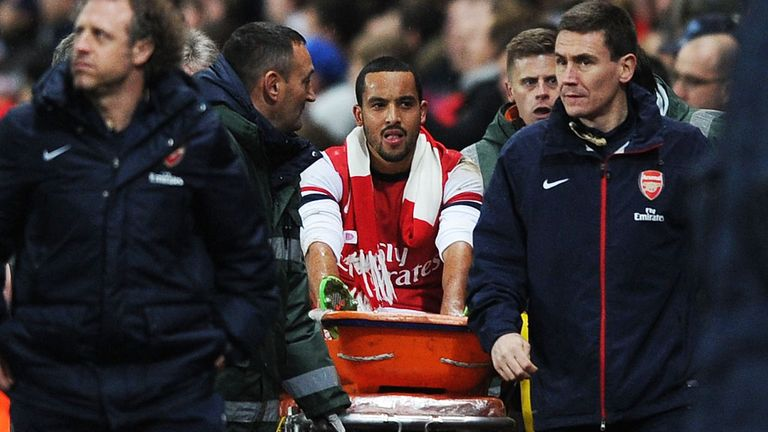 Theo Walcott: Arsenal winger is carried off against Tottenham