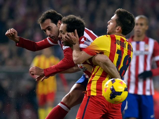 Atletico Madrid's Diego Godin vies with Jordi Alba