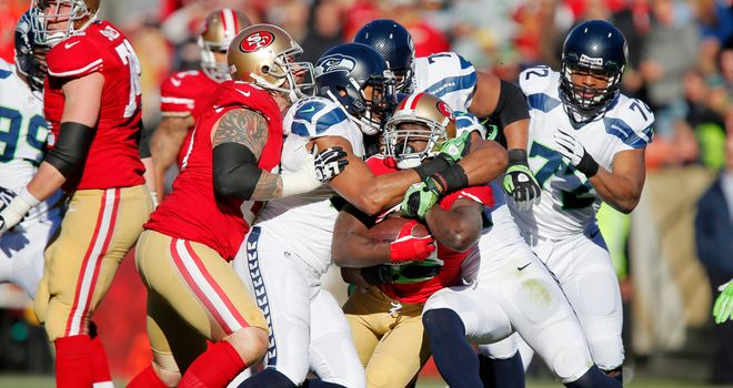 Running back Frank Gore of the San Francisco 49ers gets ganged up on by Seattle Sehawks