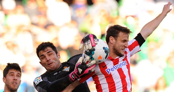 Real Betis goalkeeper Adan just about gathers the ball
