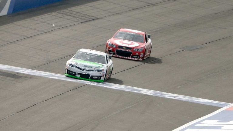 Kyle Busch leads Kyle Larson over the line to win the Auto Club 400