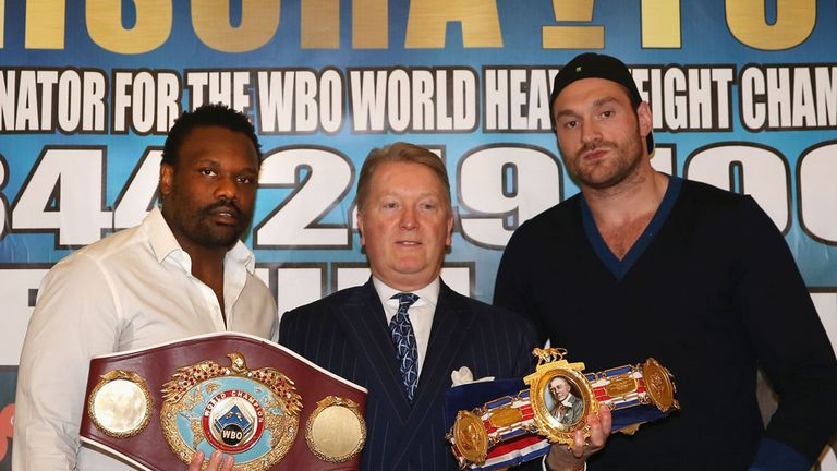 Promoter Frank Warren flanked by Dereck Chisora (L) and Tyson Fury