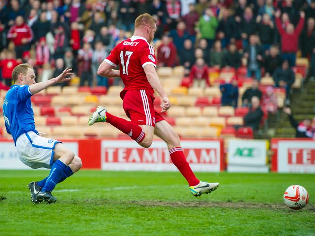 Adam Rooney prods the ball into the net after rounding keeper Alan Mannus
