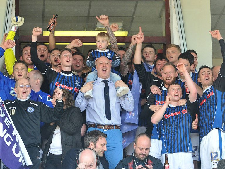 Rochdale players and staff celebrate after securing promotion