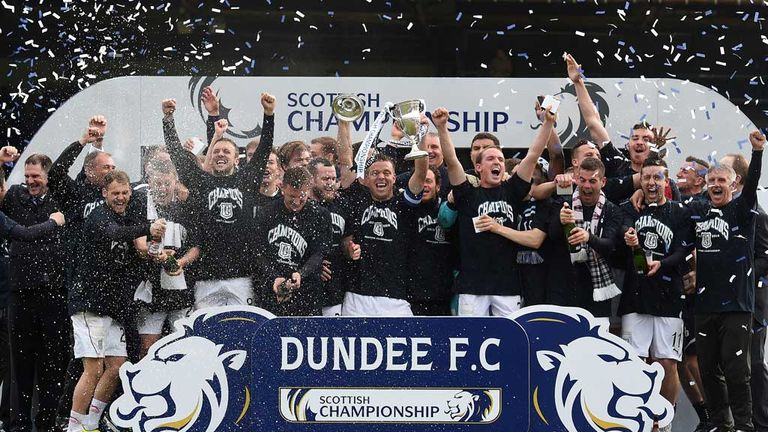 Dundee players and staff celebrate with the Scottish Championship trophy