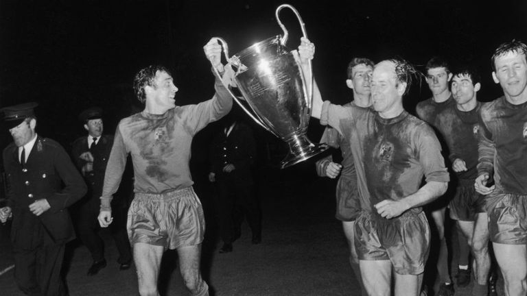 Sir Bobby Charlton (right) holds the European Cup aloft after victory over Benfica