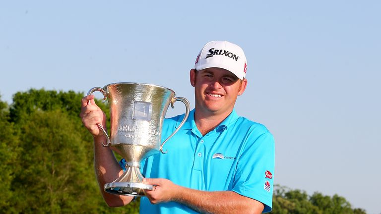 J.B. Holmes celebrates with the trophy after winning the Wells Fargo Championship
