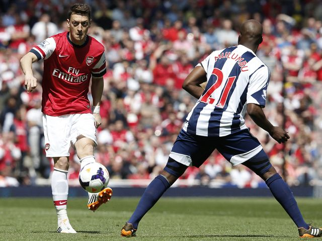 Arsenal midfielder Mesut Ozil passes the ball over West Brom's Youssouf Mulumbu