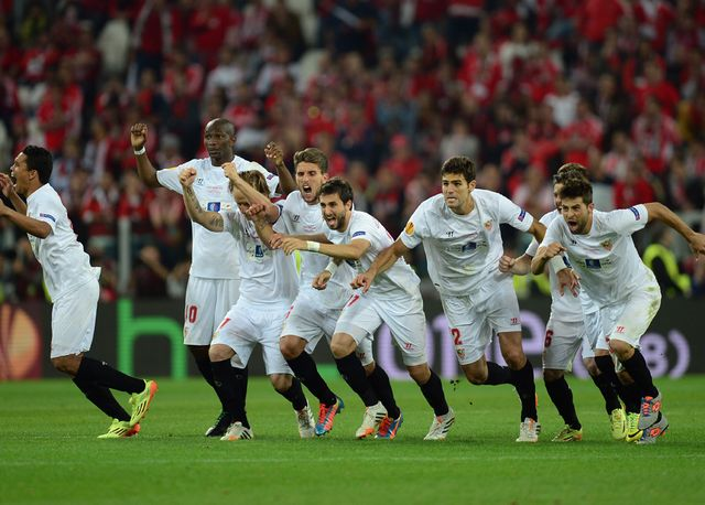 Sevilla players celebrate after Kevin Gameiro scores the winning penalty