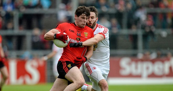 Ciaran McGinley, pictured tackling Niall Madine, netted in either half for Tyrone in Newry