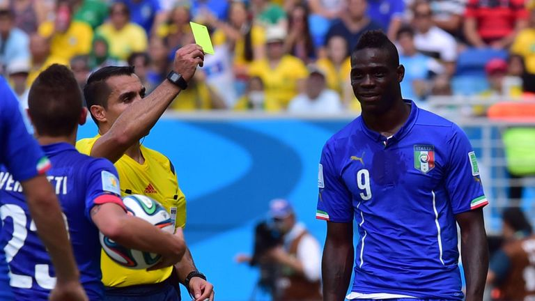 Balotelli is booked during Italy's defeat to Uruguay.